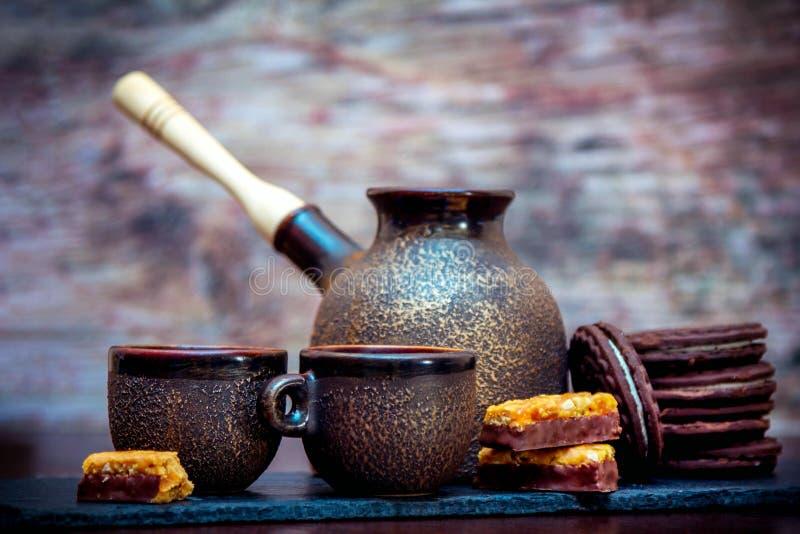 Tasses de style de cru, pot de brassage de café et biscuits et sucreries en céramique de chocolat photo libre de droits