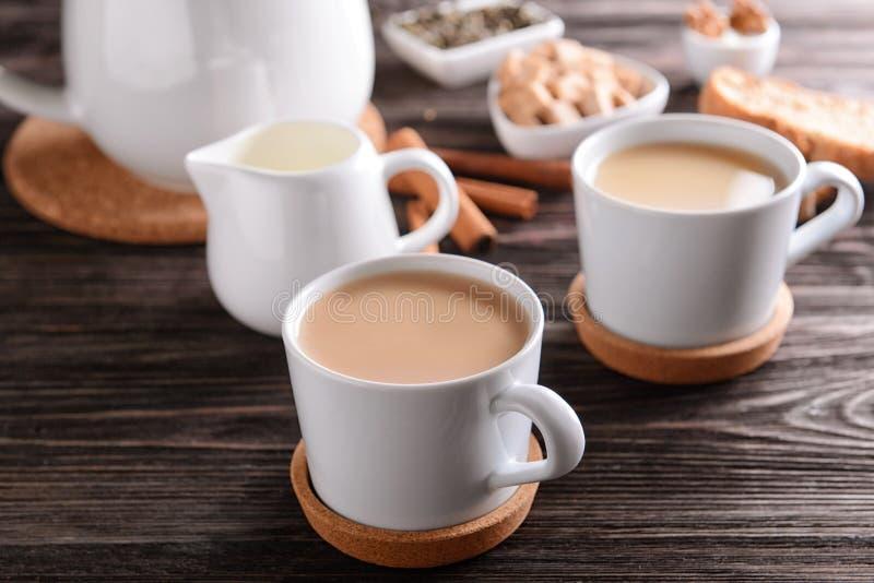 Tasses de thé au lait aromatique sur la table photo stock