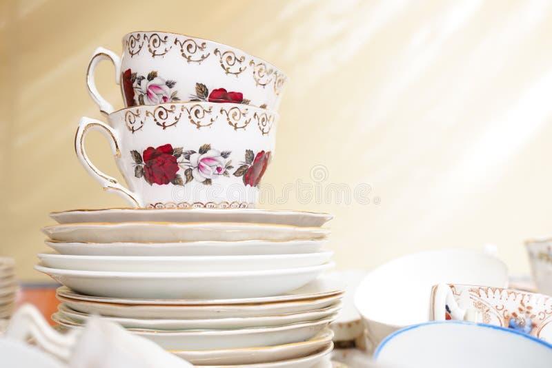 Tasses de thé et soucoupes anglaises de porcelaine de vintage avec la rose et l'écoulement images stock