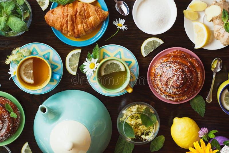 Tasses de tisane avec le citron et les feuilles en bon état, de racine de gingembre et de pâtisseries sur le fond en bois image stock