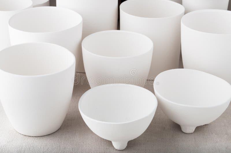 Tasses en céramique d'argile blanc fait main sur le fond de toile de chiffon images libres de droits