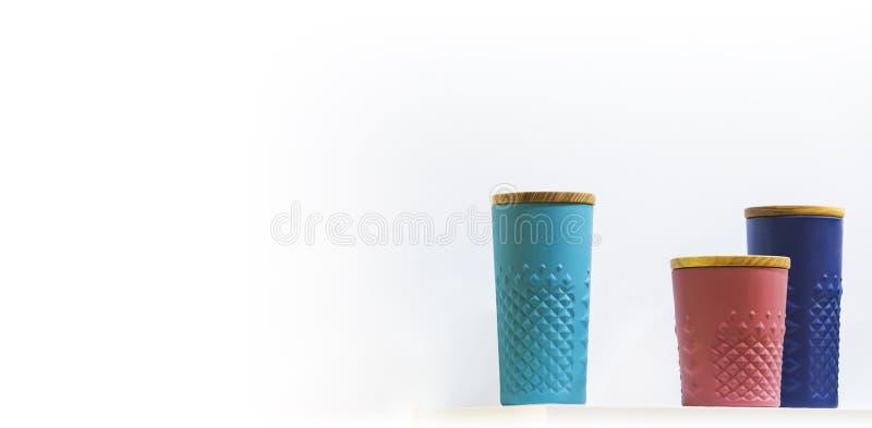 Tasses en céramique de couleur avec un couvercle pour le café sur le fond blanc photographie stock