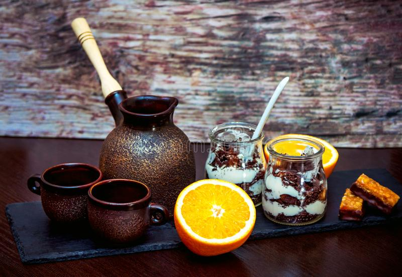 Tasses en céramique de style de cru, pot de brassage de café, orange fraîche, dessert de tiramisu dans des pots en verre photo stock