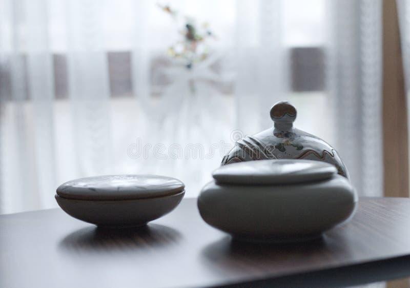Tasses en céramique de vintage sur le fond de table et de rideau - décorations d'intérieurs photos stock