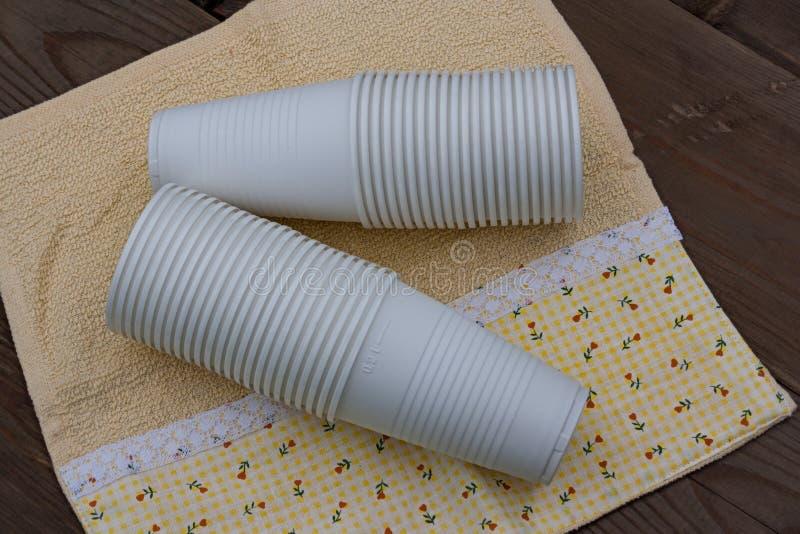 Tasses en plastique sur le fond en bois image libre de droits