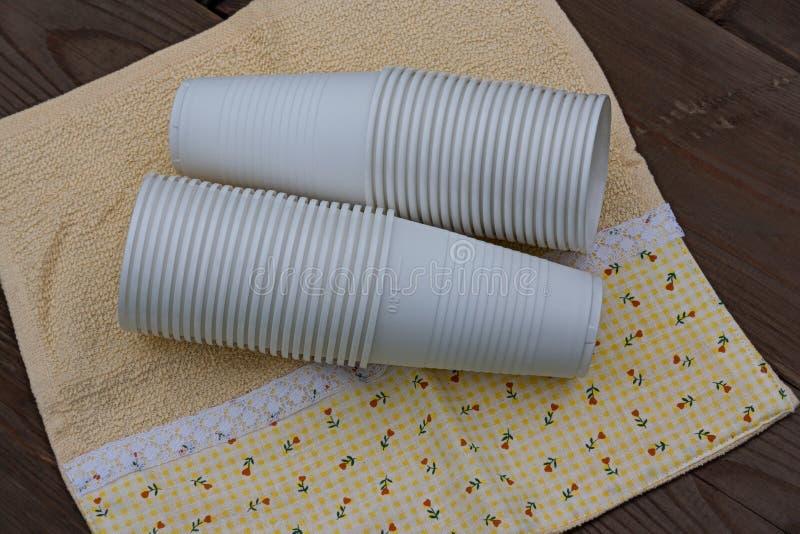 Tasses en plastique sur le fond en bois photographie stock libre de droits