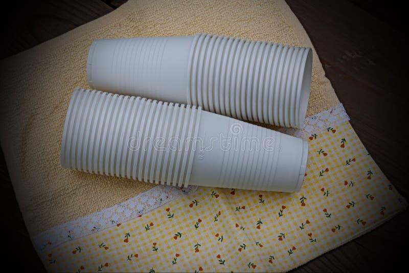 Tasses en plastique sur le fond en bois images libres de droits