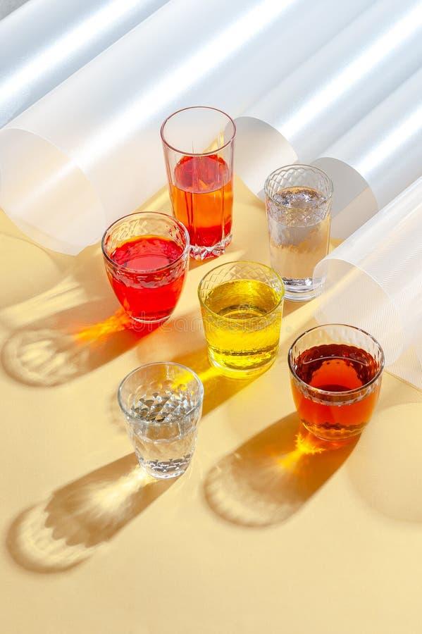 Tasses en verre avec les boissons froides multicolores sur un fond jaune tir avec la lumi?re dure photo stock