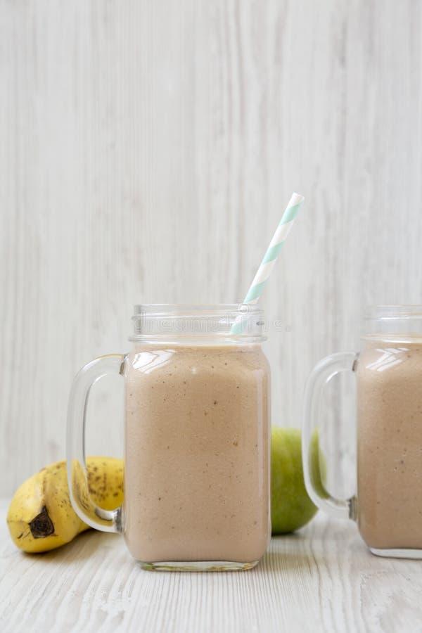 Tasses en verre de pot de ma?on remplies de smoothie de pomme de banane, vue de c?t? Plan rapproch? photographie stock