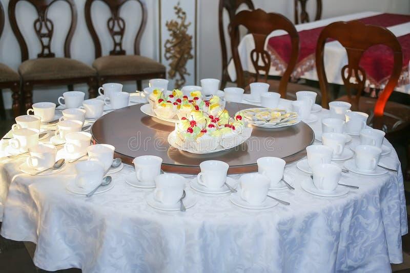 Tasses et gâteau de thé sur la table image stock