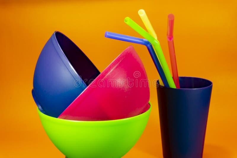 Tasses et pailles en plastique de cuvettes sur le fond orange images libres de droits