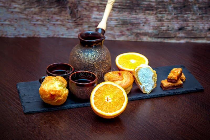 Tasses, pot de brassage de café, orange, profiterole ou gâteaux et sucreries en céramique d'eclair images stock