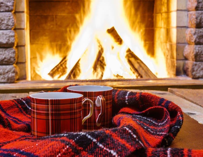 Tasses rouges pour le thé chaud et l'écharpe chaude confortable près de la cheminée photo libre de droits