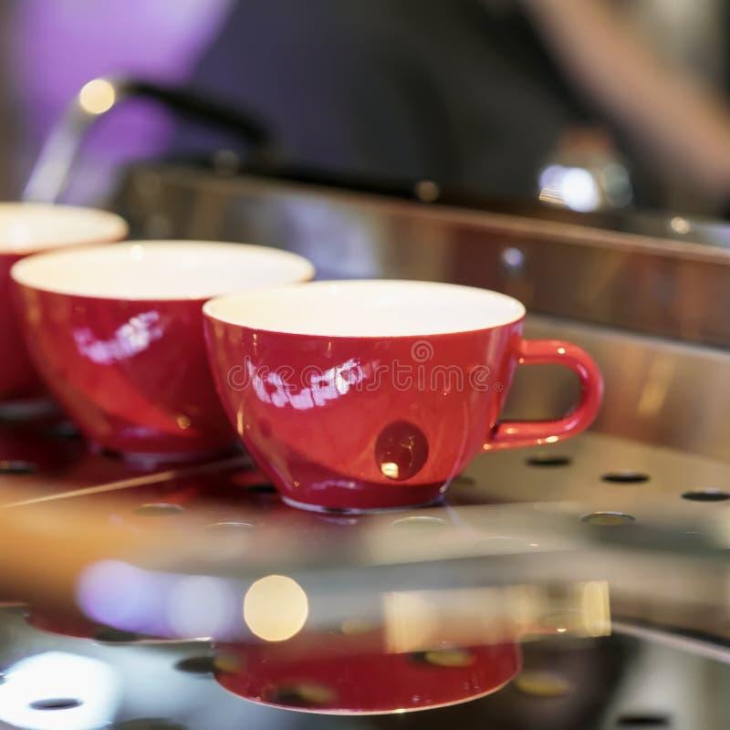 Tasses rouges sur le support de la machine de café, barre Ton foncé de vintage, temps de café, fond carré Culture de café photos stock