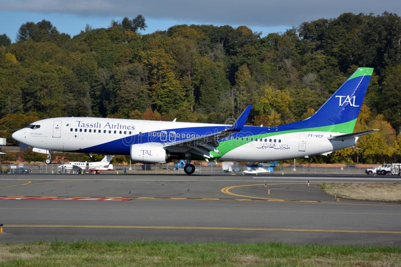 Tassili Airlines latest Boeing 737-800 on touchdown with green forest backdrop royalty free stock photos