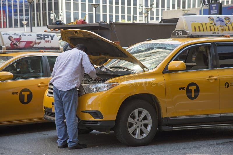Tassista giallo che esamina motore del suo taxi fotografia stock