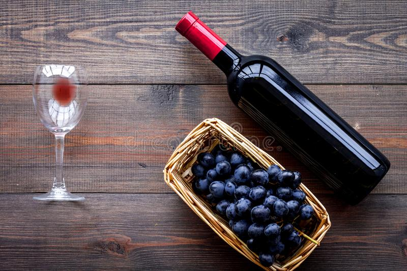 Taste red wine. Bottle of red wine, glass and black grape on dark wooden background top view stock photography