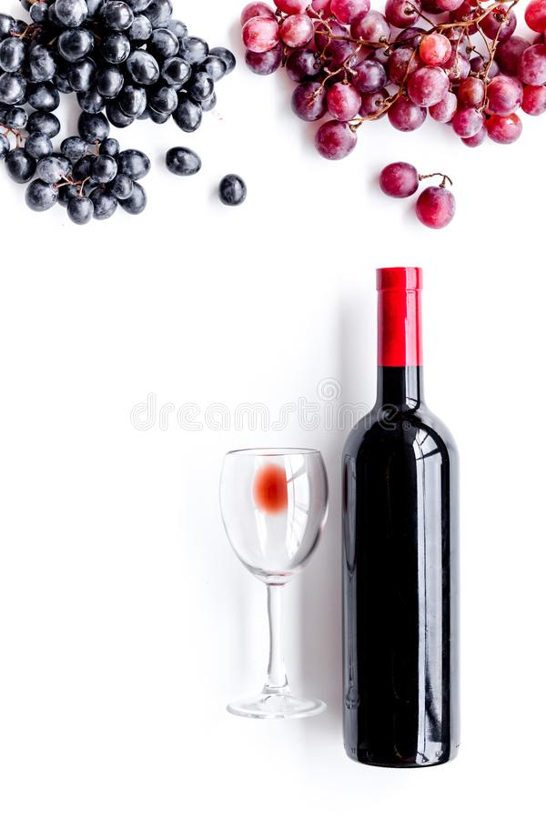 Taste red wine. Bottle of red wine, glass and black grape on white background top view copyspace. Taste red wine. Bottle of red wine, glass and black grape on royalty free stock image