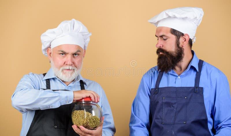 Taste unroasted coffee. culinary concept. Perfect sort of coffee. professional barista. restaurant cook. mature senior. Bearded men in uniform. barista men stock photo
