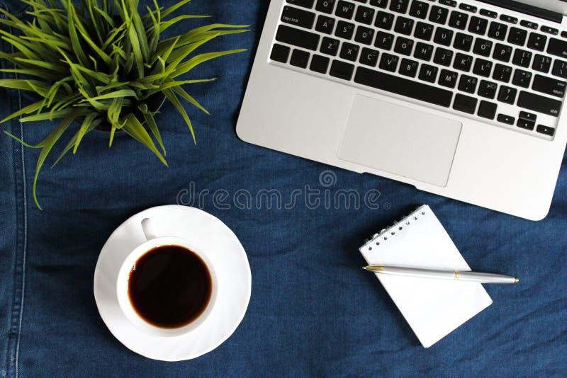 Tastiera del computer portatile, tazza bianca di tè sul piattino, blocco note, penna e pianta verde nell'angolo sul fondo sgualci fotografia stock