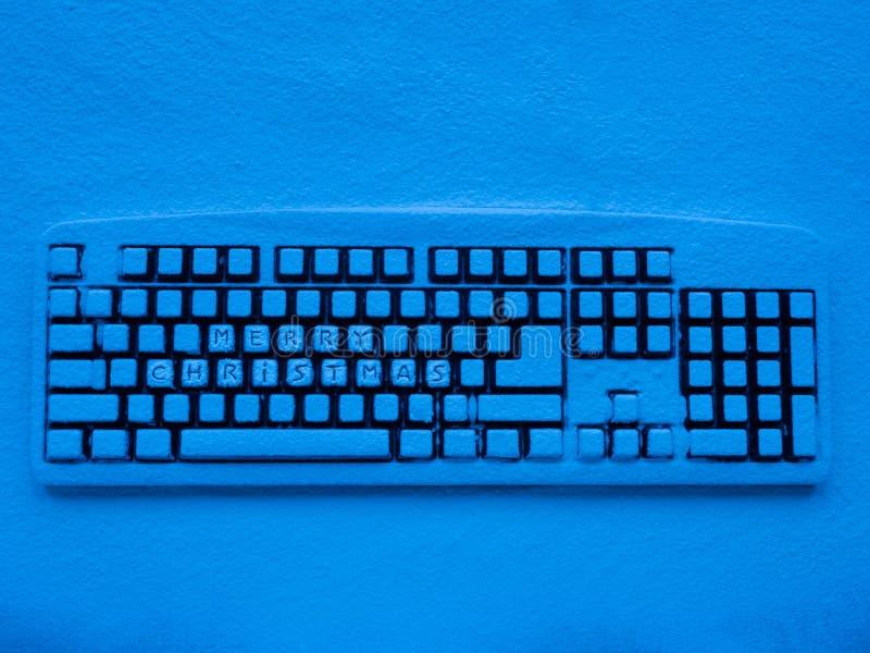 Tastiera di computer senza fili coperta di neve illuminata da luce al neon blu con il Buon Natale di titolo immagini stock libere da diritti