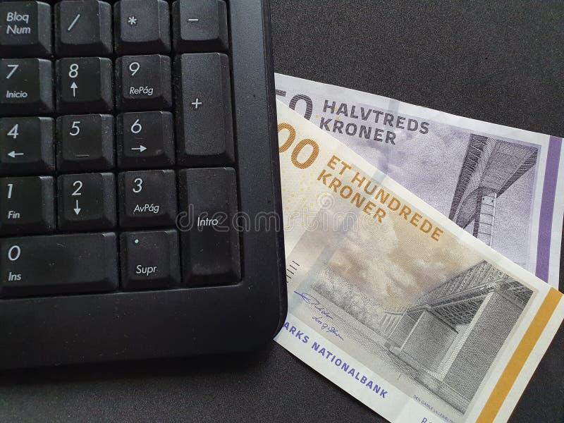 tastiera numerica del computer e soldi danesi sulla tavola nera fotografia stock
