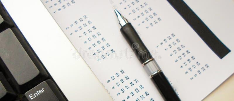 Tastiera, penna e calendario sulla tavola workplace fotografia stock libera da diritti