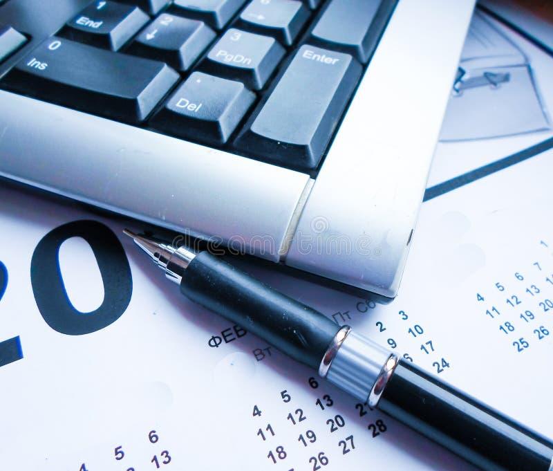 Tastiera, penna e calendario sulla tavola workplace immagini stock libere da diritti