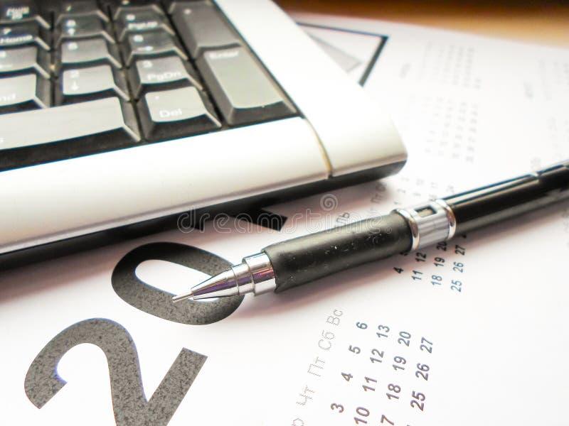 Tastiera, penna e calendario sulla tavola workplace immagini stock