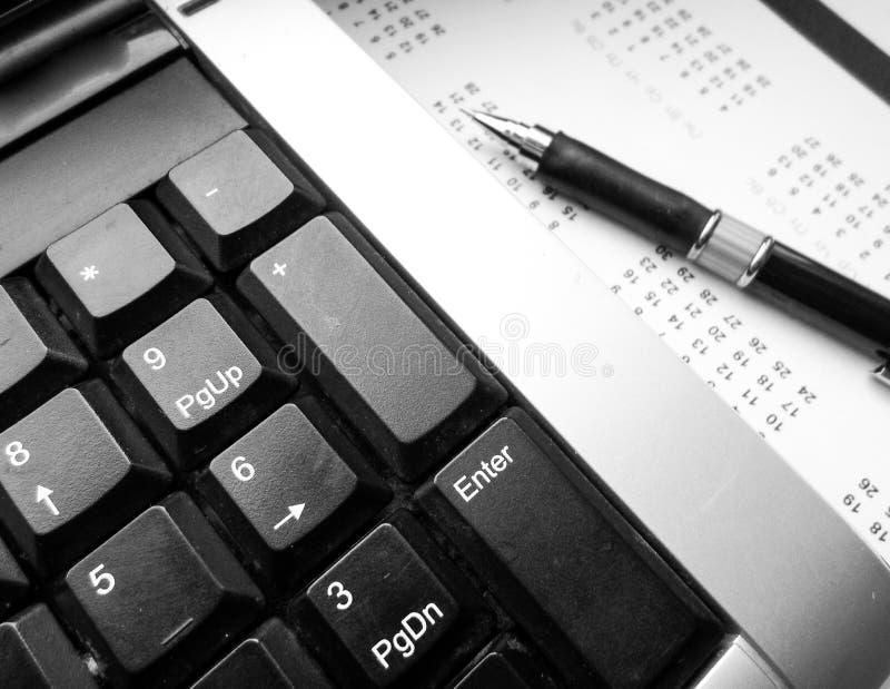 Tastiera, penna e calendario sulla tavola workplace fotografie stock
