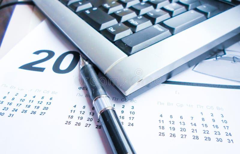 Tastiera, penna e calendario sulla tavola workplace immagine stock libera da diritti