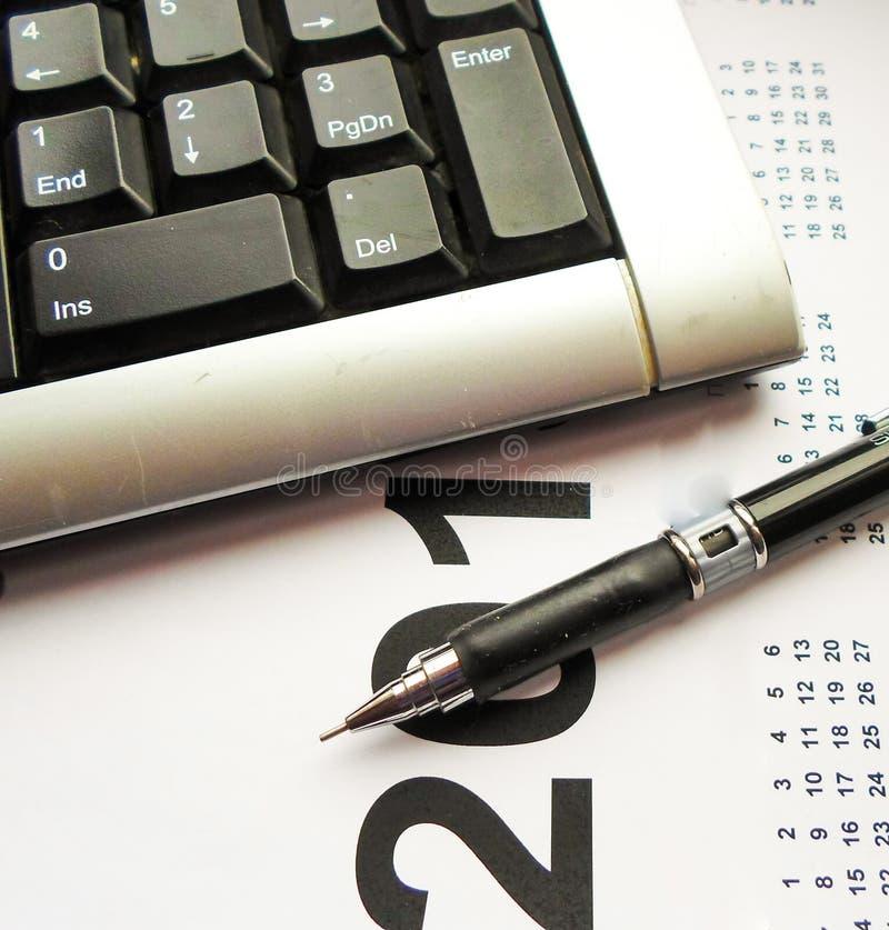 Tastiera, penna e calendario sulla tavola workplace immagine stock