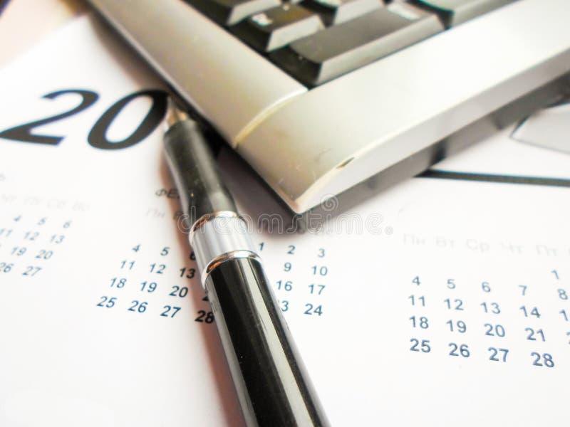 Tastiera, penna e calendario sulla tavola workplace fotografia stock
