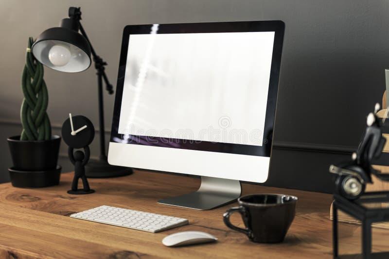 Tastiera, topo e desktop computer sullo scrittorio di legno con la lampada dentro immagini stock