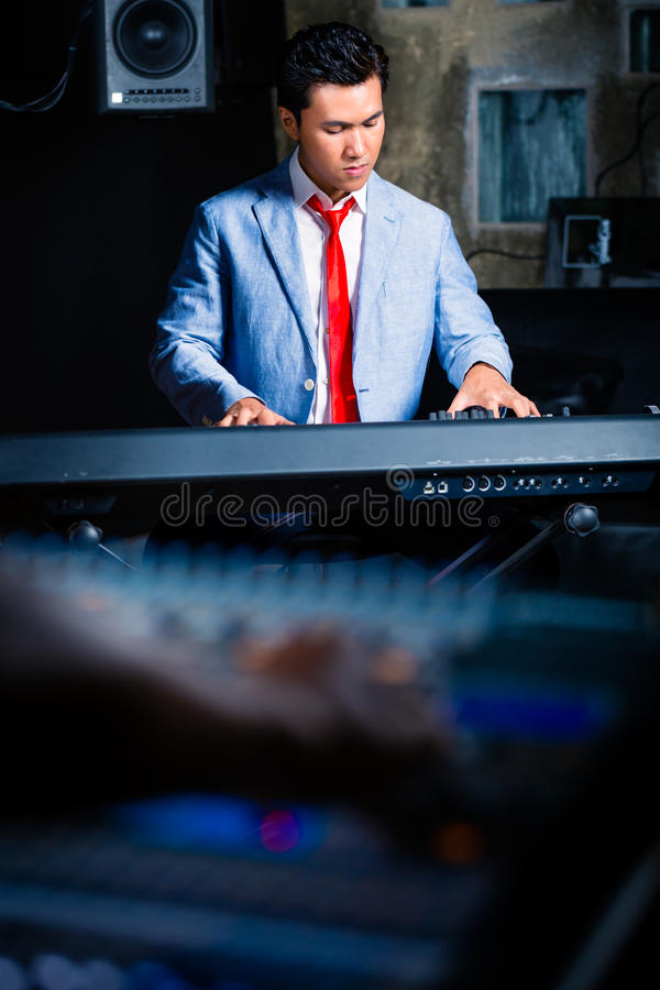 Tastierista asiatico che gioca nello studio di registrazione fotografia stock