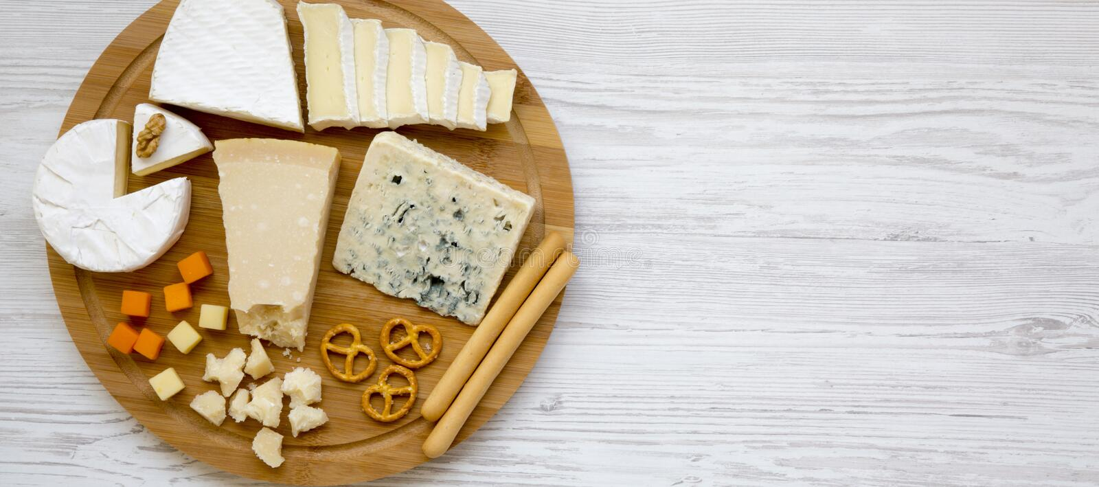 Tasting cheese with bread sticks, walnuts and pretzels on a bamboo board on a white wooden background, top view. Food for wine. Copy space. From above stock photography