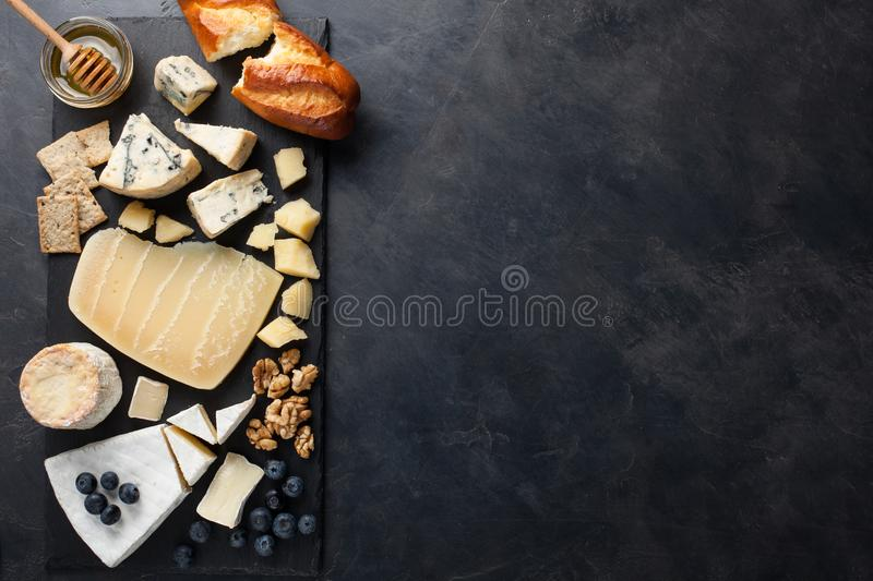 Tasting cheese dish on a dark stone plate. Food for wine and romantic date, cheese delicatessen on a black concrete background. To. P view with copy space royalty free stock images