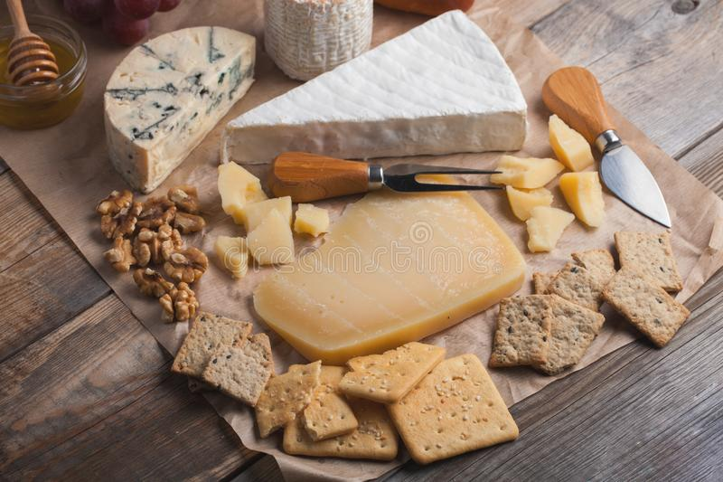 Tasting cheese dish on a wooden plate. Food for wine and romantic, cheese delicatessen on a wooden rustic table. Top view.  royalty free stock images