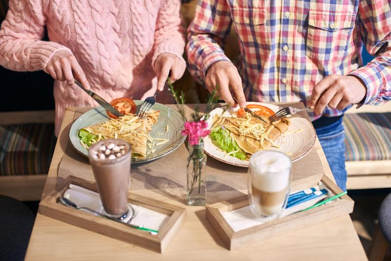 Tasting with delicious food at dinning table served with beverages and flower on foreground. Cropped general view. stock images