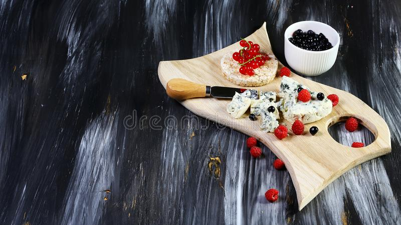 Tasting mold cheese with fruits and fresh berries raspberries, blueberries on stone dark black background stock image