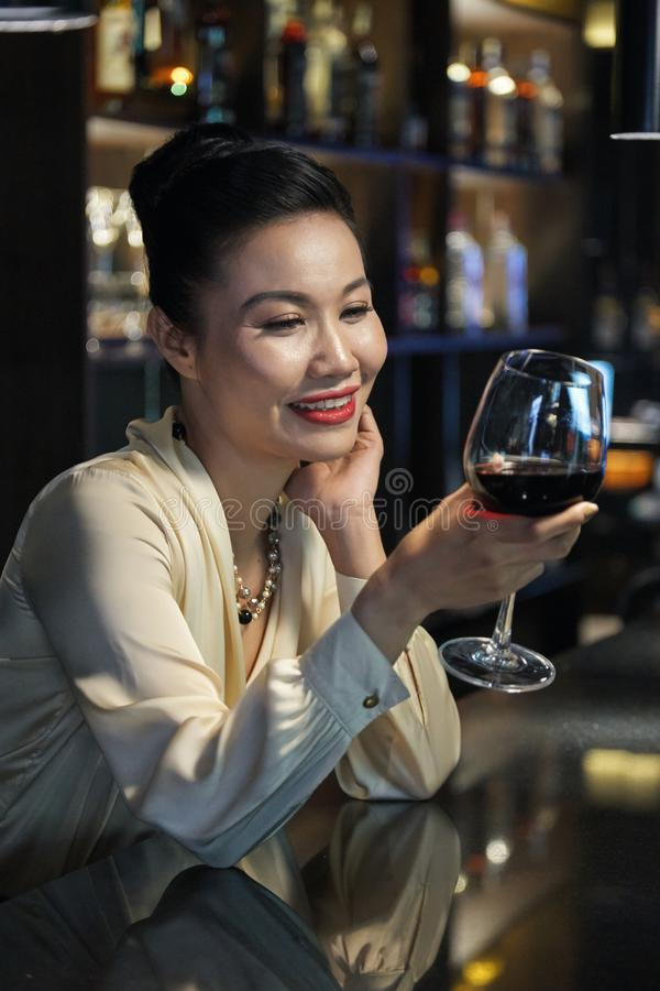 Tasting wine. Attractive Vietnamese restaurant owner tasting wine at bar counter stock photography