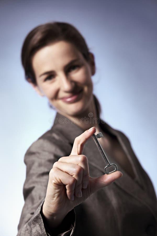 Tasto astuto della holding della donna di affari fra le barrette immagine stock