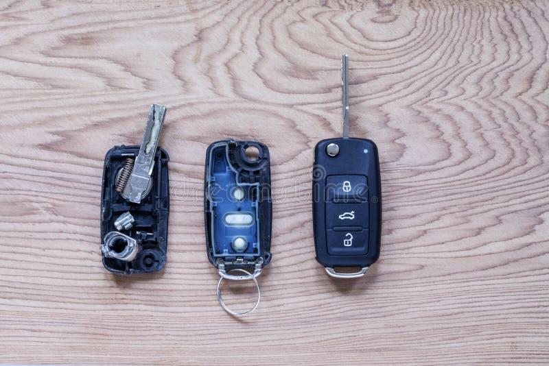 Tasto remoto rotto o danneggiato fob e chiave del nuovo veicolo su fondo di legno Fob dei tasti remoti danneggiati o danneggiati  fotografie stock libere da diritti