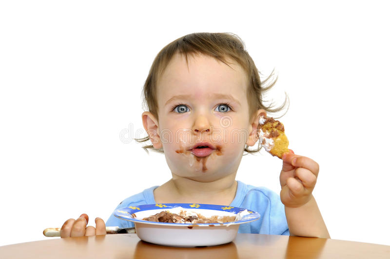 Tasty. Beautiful blue eyed baby eating icecream with a spoon isolated in white royalty free stock photos