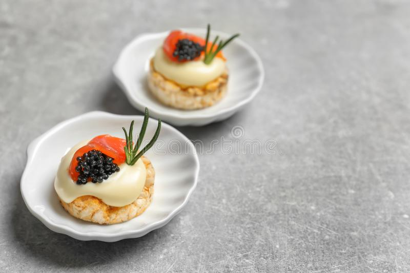 Tasty appetizer with black caviar and salmon on plates royalty free stock photos