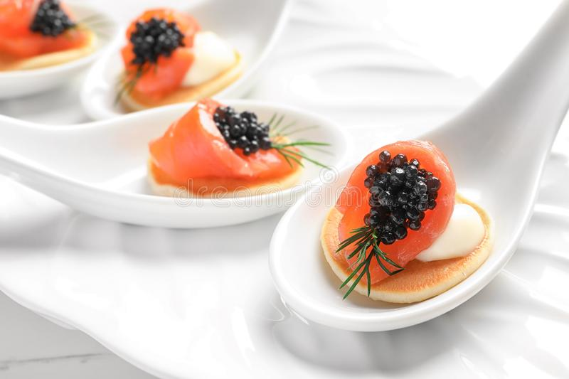 Tasty appetizers with black caviar and salmon stock image