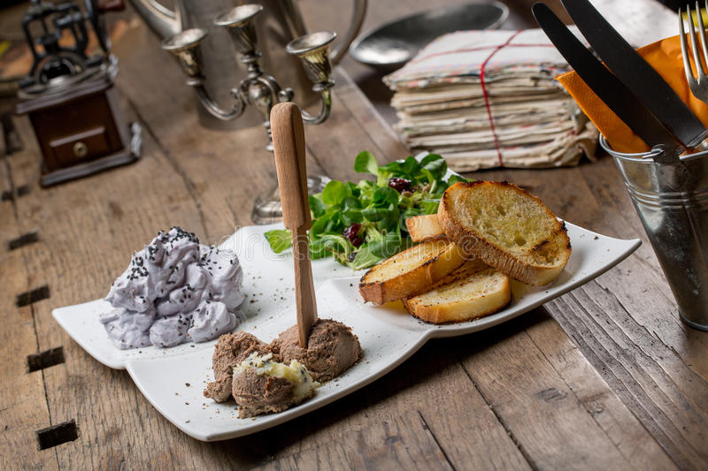 Tasty appetizers with chicken liver pate, valerian salad, toasted bread and blueberry mousse royalty free stock photo