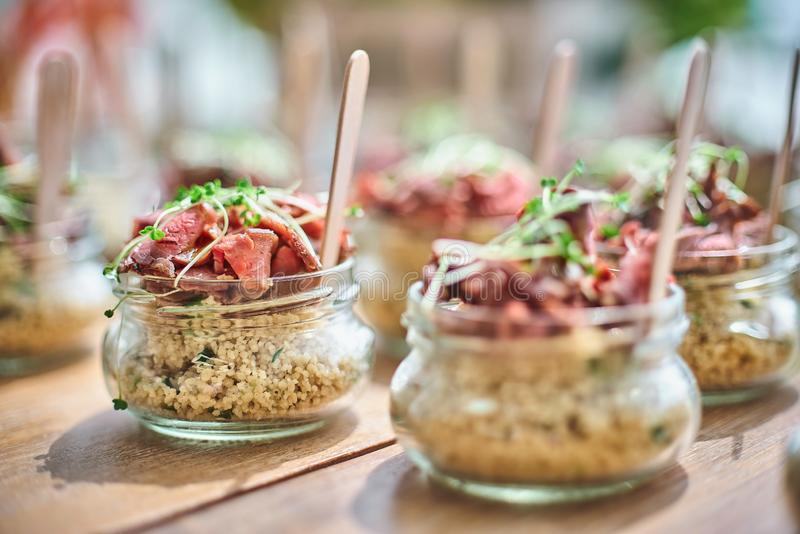 Tasty appetizers with wooden spoons served in glass jars on wooden table. Tasty appetizers served in glass jars on wooden table. Concept for Catering, selective royalty free stock image