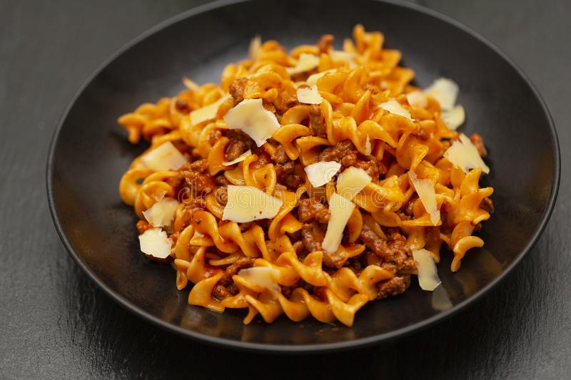 Tasty appetizing classic Italian Fusilli pasta with tomato sauce, cheese Parmesan, beef and basil in black bowl on table. royalty free stock image