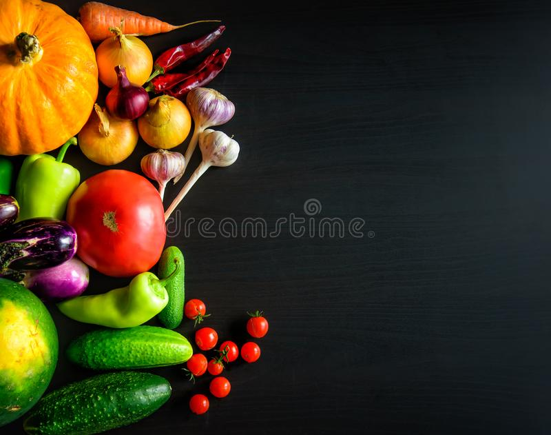 Tasty appetizing fresh autumn seasonal vegetables on dark wooden background top view with copy space. Healthy food, vegetarianism royalty free stock image